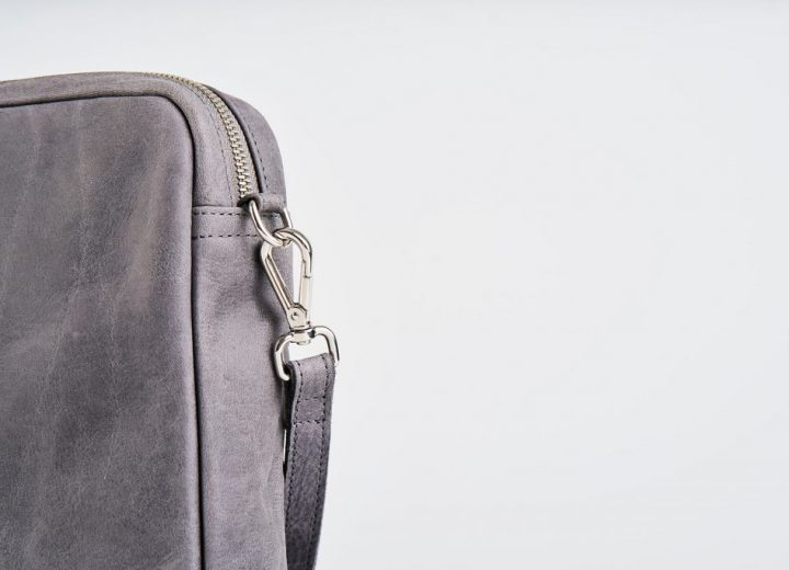 Zoom on a product Picture front side view of a standing up blue vegetable tanned leather shoulder bag with a double silver zipper opening and an detachable shoulder strap