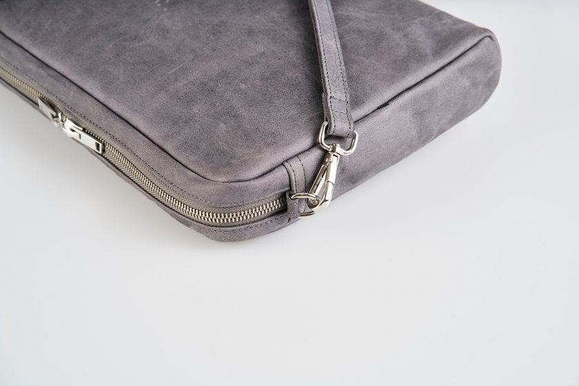 Zoom Product Picture side top view of a lying down blue vegetable tanned leather shoulder bag with a double silver zipper opening and an detachable shoulder strap lying on top of the bag