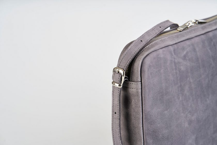 Product Picture front side view of a standing up blue vegetable tanned leather shoulder bag with a double silver zipper opening and an adjustable and detachable shoulder strap