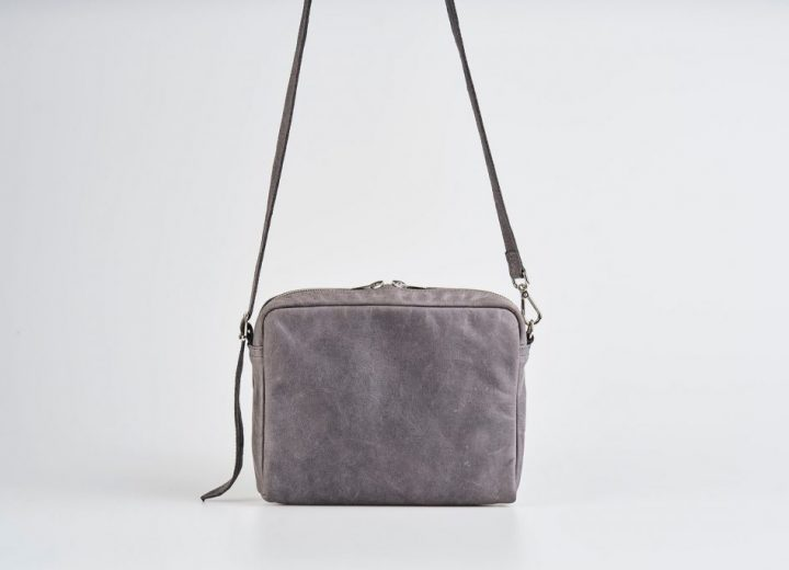 Product Picture front view of a standing up blue vegetable tanned leather small shoulder bag with a double silver zipper opening with a adjustable strap hanging straight in the air
