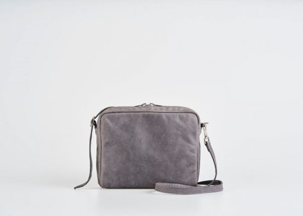 Product Picture front view of a standing up blue vegetable tanned leather small shoulder bag with a double silver zipper opening with a adjustable strap hiding behind the bag