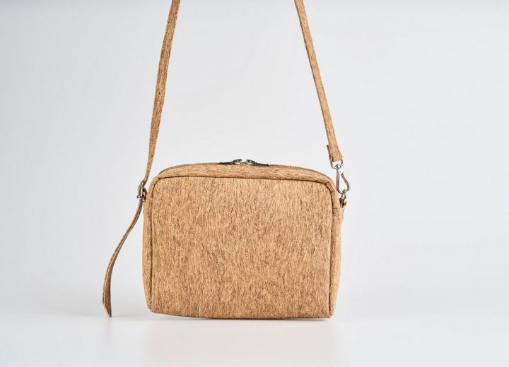 Product Picture front view of a standing up natural cork patterned small shoulder bag with a double silver zipper opening with a adjustable strap hanging straight in the air