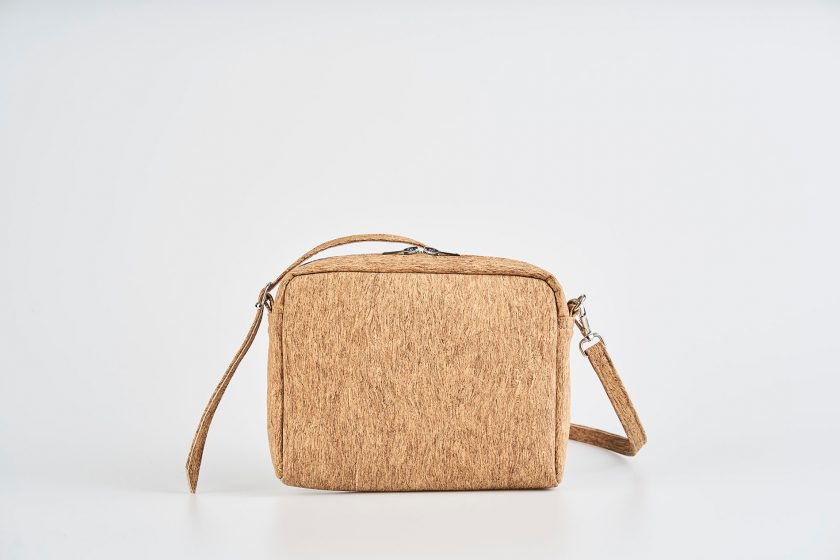 Product Picture front view of a standing up natural cork patterned small shoulder bag with a double silver zipper opening with a adjustable strap hiding behind the bag