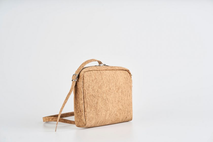 Product Picture front right side view of a standing up natural cork patterned small shoulder bag with a double silver zipper opening and a adjustable strap