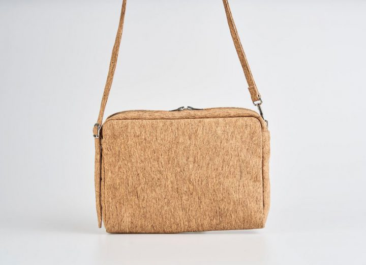 Product Picture front view of a standing up natural cork patterned shoulder bag with a double silver zipper opening with a adjustable strap hanging straight in the air