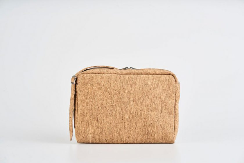 Product Picture front view of a standing up natural cork patterned shoulder bag with a double silver zipper opening with a adjustable strap hiding behind the bag