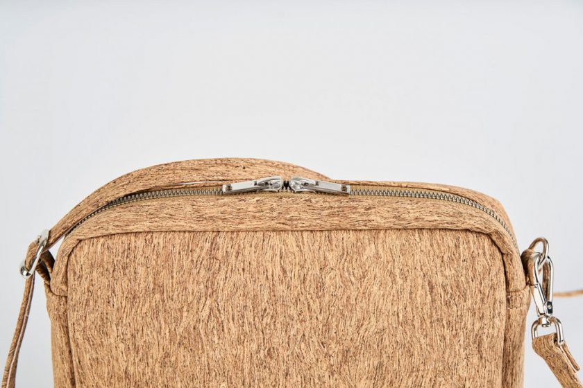 Zoom on a Product Picture view of a standing up natural cork patterned shoulder bag with a double silver zipper opening and an adjustable and detachable shoulder strap with a hook on one side and a buckle at the other side