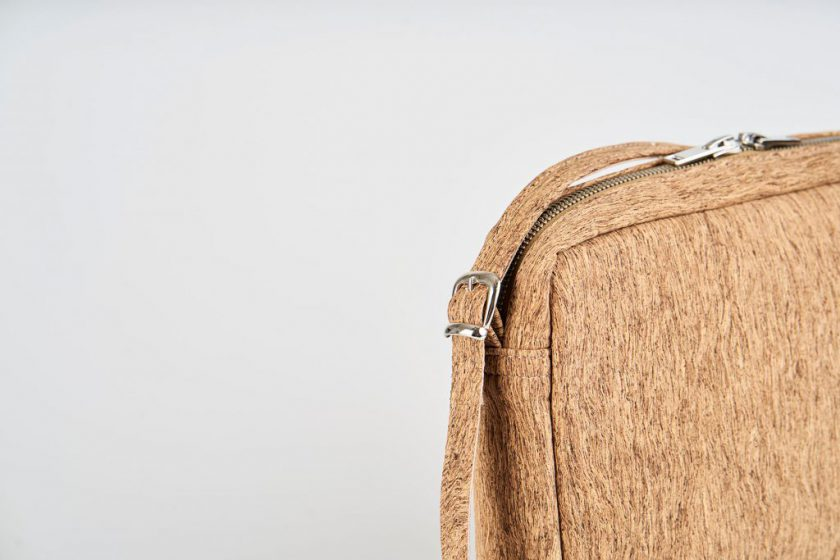 Product Picture front side view of a standing up natural cork patterned shoulder bag with a double silver zipper opening and an adjustable and detachable shoulder strap