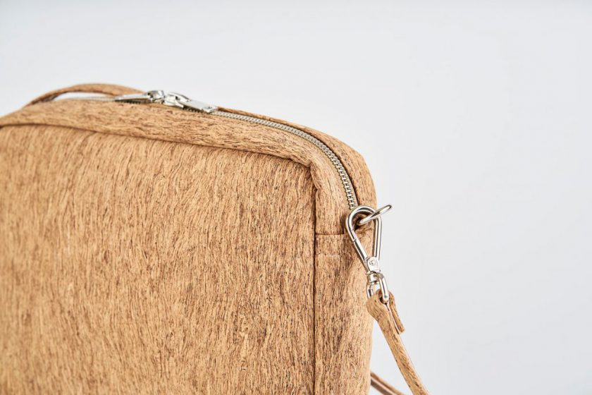 Zoom on a product Picture front side view of a standing up natural cork patterned shoulder bag with a double silver zipper opening and an detachable shoulder strap