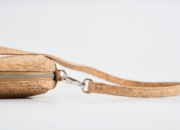 Zoom Product Picture top view of a natural cork patterned shoulder bag with a silver zipper opening and an detachable shoulder strap lying on top of the bag