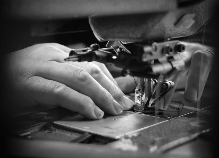 black and white picture of an closeup of a hand sewing with an industrial sewing machine