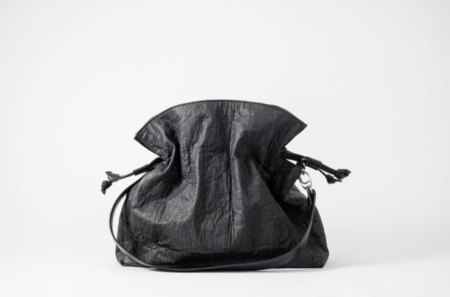 Front view on an closed black Pinatex Bucket-Tote bag with a detachable shoulder strap made of vegan leather dropped in front of the bag and a drawstring on each side of the bag which are pulled together