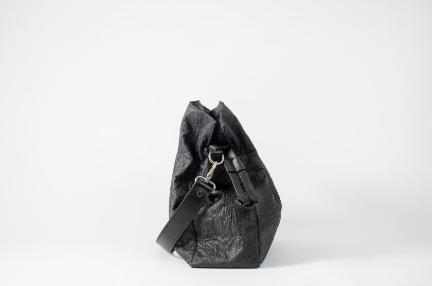 Side view on an closed black Pinatex Bucket-Tote bag with a detachable shoulder strap made of vegan leather dropped in front of the bag and a drawstring on the side of the bag