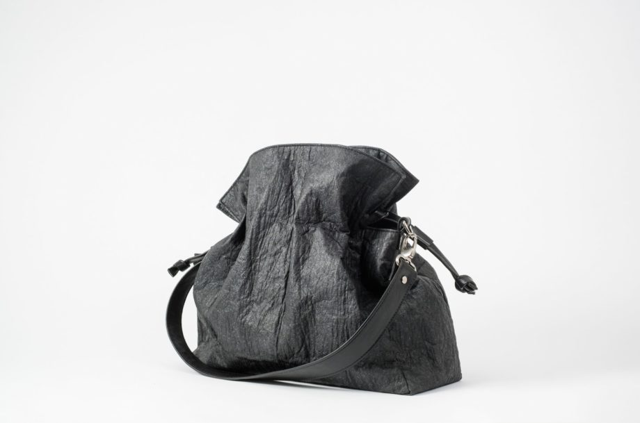 Side front view on an closed black Pinatex Bucket-Tote bag with a detachable shoulder strap made of vegan leather dropped in front of the bag and a drawstring on each side of the bag which are pulled together