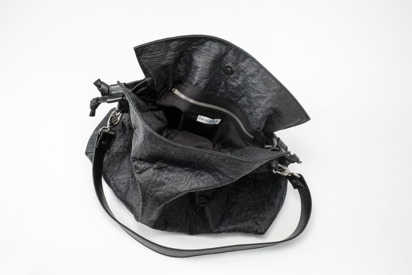 Top view on an open black Pinatex Bucket-Tote bag with a zip pocket and a white label sewn in the lining and a detachable shoulder strap made of vegan leather and a drawstring on each side of the bag