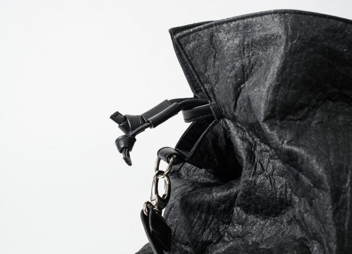 Zoom on the side top of a black Pinatex Bucket-Tote bag with a a drawstring with two knots and a hook with a shoulder strap made of vegan leather attached to a D-Ring