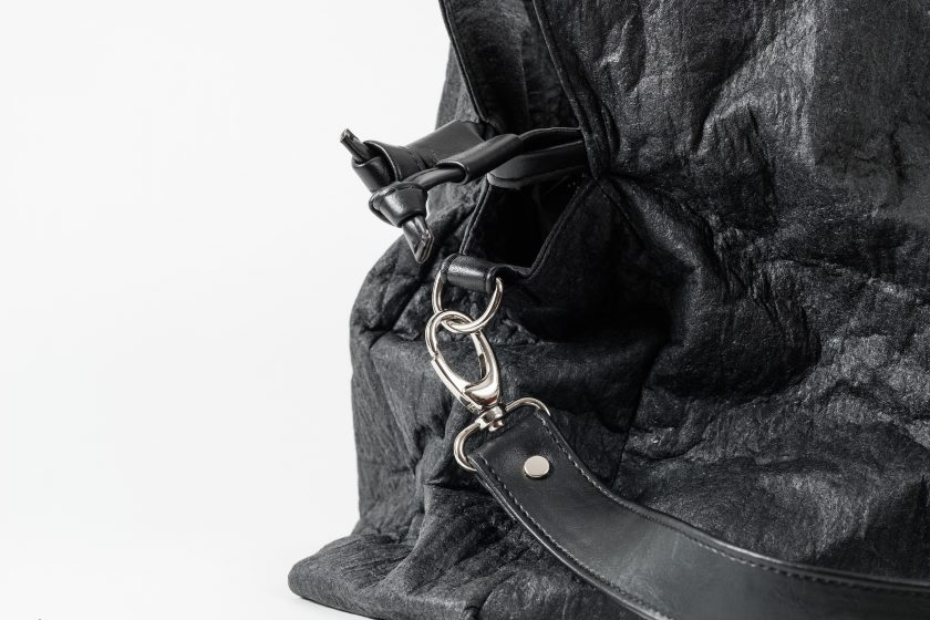 Zoom on the side of a black Pinatex Bucket-Tote bag with a a drawstring and a hook with a shoulder strap made of vegan leather attached to a D-Ring