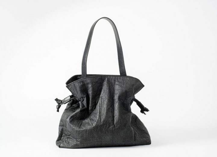 Front view on a standing up closed black Pinatex Bucket-Tote bag with a a drawstring on each side and a larger shoulder strap made of vegan leather