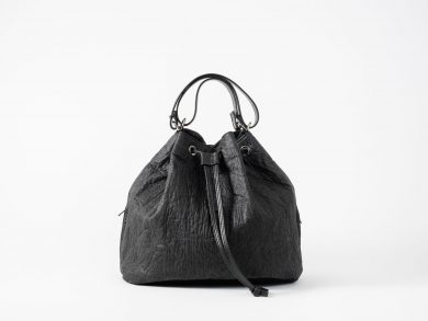 Front view on a standing up closed black Pinatex Bucket Bag with a zip pocket sewn in each side seam, a three times folded adjustable handle made of vegan leather and a drawstring knotted in the front
