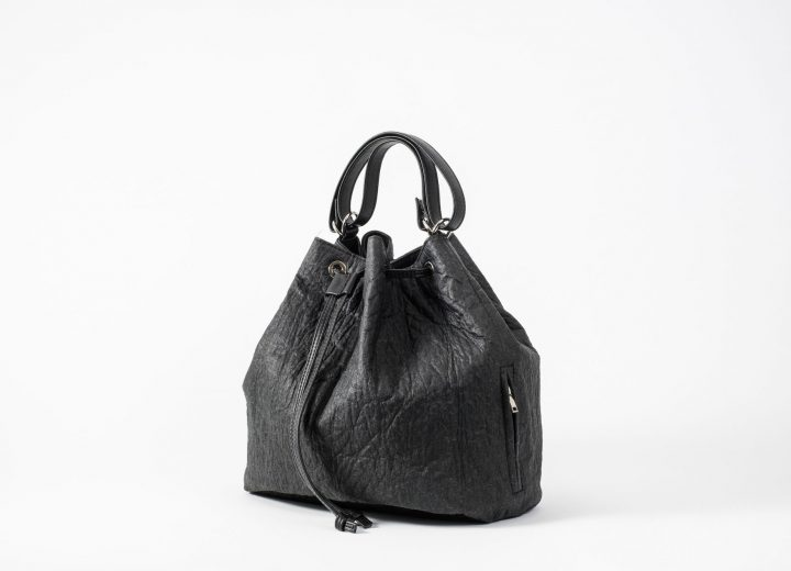 Side front view on a standing up closed black Pinatex Bucket Bag with a zip pocket sewn in the side seam, a three times folded handle made of vegan leather and a drawstring knotted in the front