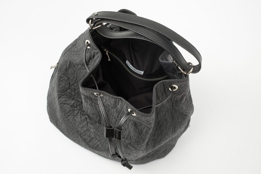 Top view on an open black Pinatex Bucket Bag with a zip pocket and a white label sewn in the lining and a three times folded adjustable handle made of vegan leather and a drawstring knotted in the front