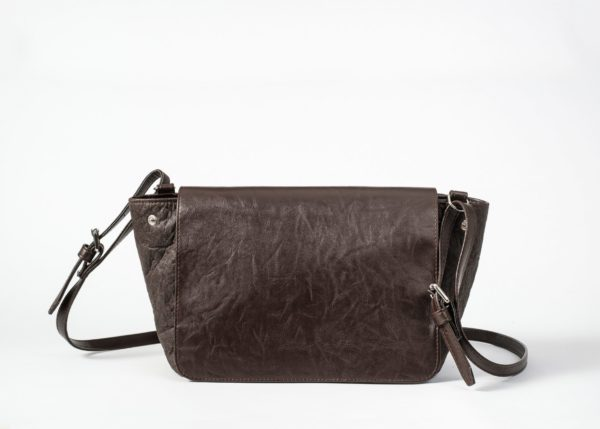 Front view of the closed brown shoulder bag where as the body with its open sides and visible press button is made of pinatex and the string which is adjustable on both sides and the closed flap cover are made of vegan leather