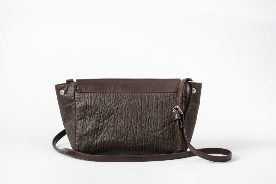Back view of the brown shoulder bag with open sides where as the body is made of pinatex and the adjustable string and the flap cover are made of vegan leather