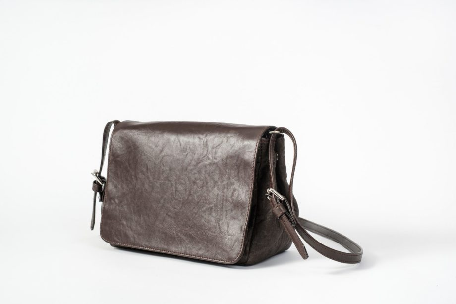 Side front view of the closed brown shoulder bag where as the body is made of pinatex and the adjustable string and the closed flap cover are made of vegan leather