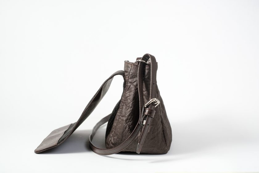 Side view of the open brown shoulder bag where as the body is made of pinatex and shows the side closed with a press button and the adjustable string and the back folded flap cover are made of vegan leather