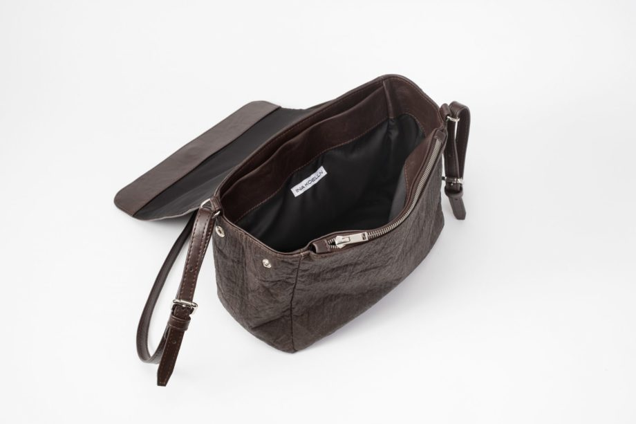 """Top side view of the open brown shoulder bag where as the body is made of pinatex and shows the side with a press button and a zip pocket sewn in the front lining and a white """"ina koelln"""" label sewn in the black lining the adjustable string is made of vegan leather"""