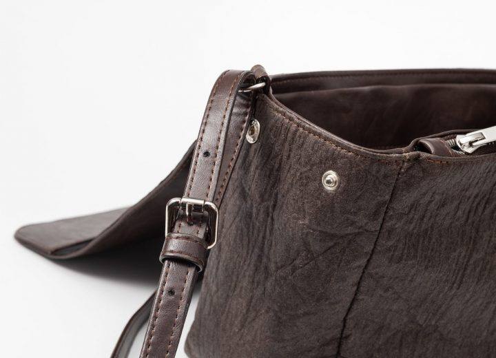 zoom of the side of the brown shoulder bag where as the body is made of pinatex and shows the side with a press button and a zip pocket sewn in the lining and the adjustable string is made out of vegan leather