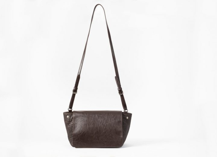 front view of an upstanding brown shoulderbag with a flap cover and adjustable string in vegan leather and the shape of the body of the bag is in Pinatex and can change volume by closing the press buttons on the sides