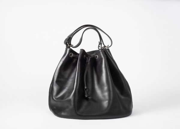 Front view on a black vegetable tanned leather Bucket Bag with a short handle folded three times and a string passing the eyelets and hanging in the front of the bag