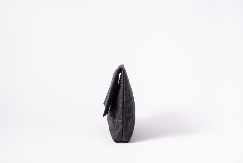 Side view on an upstanding charcoal colored Clutch with invisible magnet opening