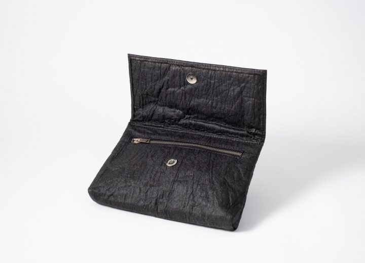 Front side view on an half standing charcoal colored Pinatex Clutch with the flap open so that you can see the magnetic button and a zip opening