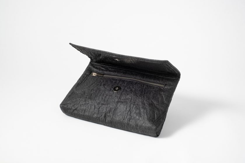 Front side view on an half standing charcoal colored Pinatex Clutch with the flap half open so that you can see the magnetic button and a zip opening