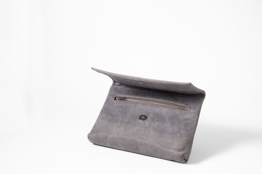 Front side view on an half standing blue-greyish vegetable tanned Leather Clutch with the flap half open so that you can see the magnetic button and a zip opening