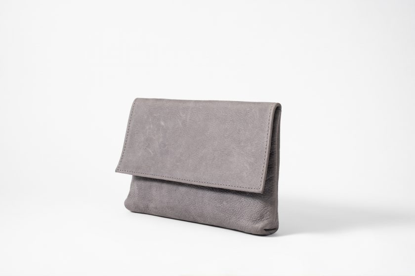 Front side view on an upstanding blue-greyish vegetable tanned Leather Clutch with invisible magnet opening