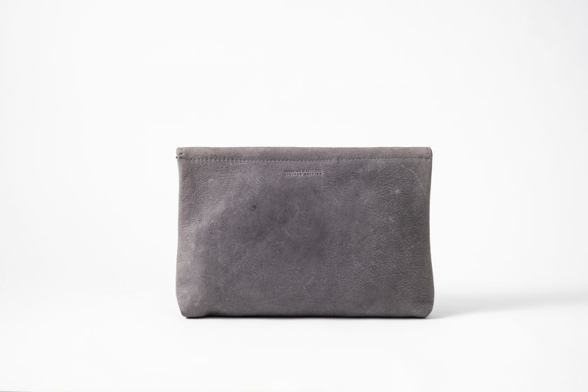 Back view on an upstanding blue-greyish vegetable tanned Leather Clutch with invisible magnet opening and only one seam in the back top of the bag