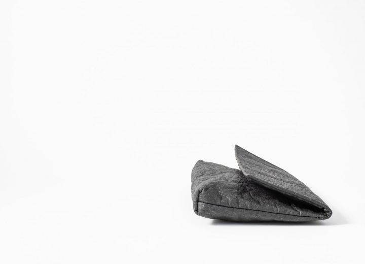 side view on a lying down Clutch made of charcoal colored Pinatex