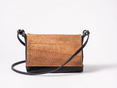 Front view on a black mini Clutch bag with a caramel colored salmon leather cover flap which is closed in the front and a black leather string knotted on each side of the bag to a D-Ring