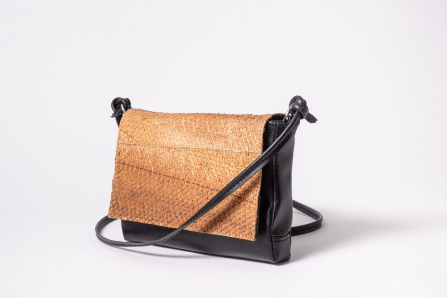 Right side front view on a black mini Clutch bag with a caramel colored salmon leather cover flap which is closed in the front and a black leather string knotted on each side of the bag to a D-Ring
