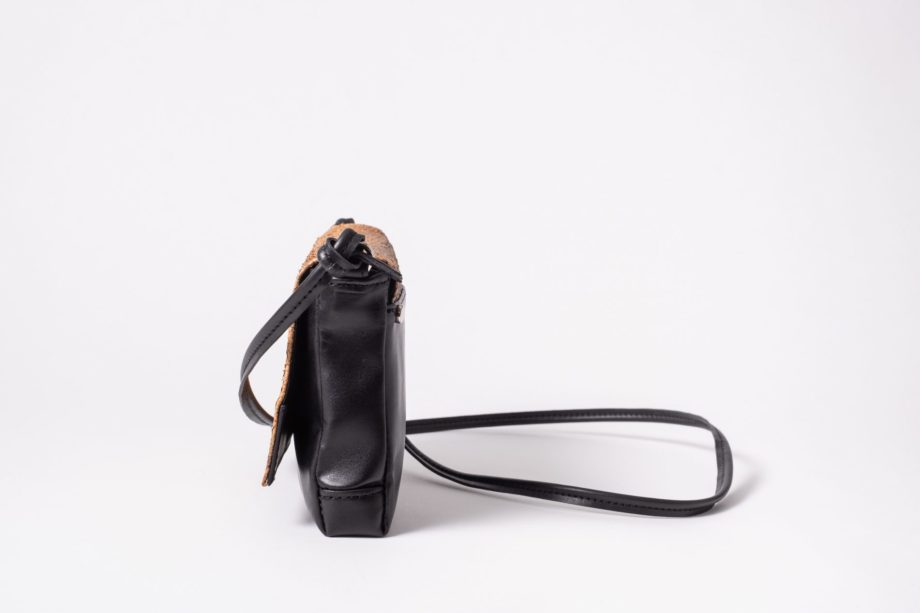 Side view on a black mini Clutch bag with a caramel colored salmon leather cover flap which is closed in the front and a black leather string knotted on the side of the bag to a D-Ring