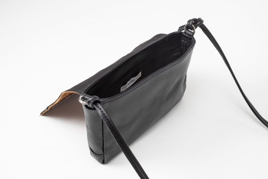 Top side view on a open black mini Clutch bag which has a white label sewn in the lining and a black leather string knotted on each side of the bag to a D-Ring