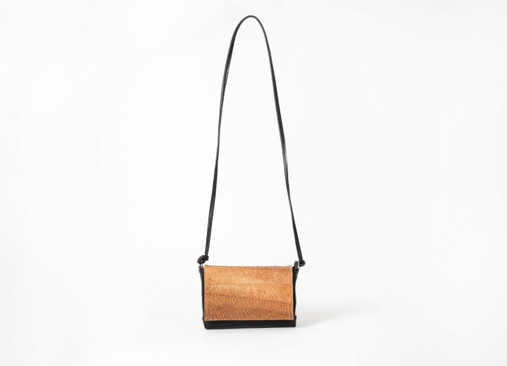 Front view on a upstanding black mini Clutch bag with a caramel colored salmon leather flap-cover closed in front with an invisible magnet and a black leather string which is knotted on each side of the clutch