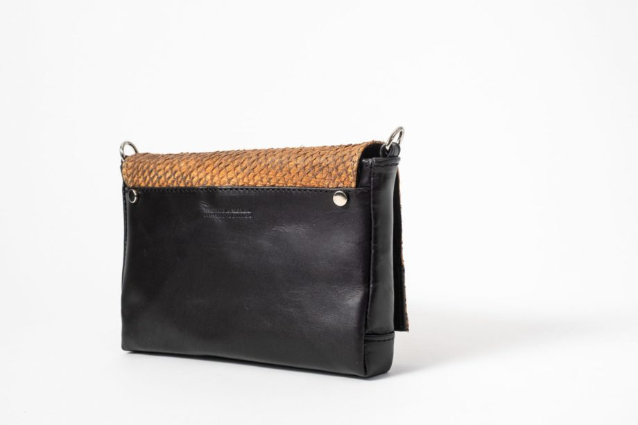 Right side back view on a black mini Clutch bag with a caramel colored salmon leather flap-cover closed in front and decorated with a rivet on each side in the back and on the side of the clutch there is a D-ring visible