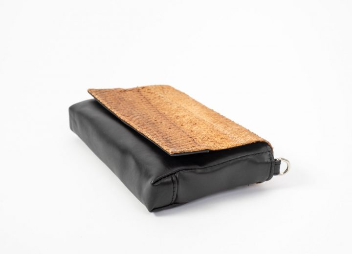 Lying flat side view on a black Clutch bag with a caramel colored salmon leather flap-cover closed in front and on the right side of the clutch there is a D-ring visible