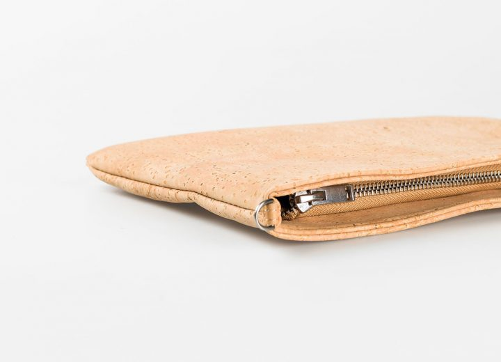 Zoom in on a cork pouch in a light natural pattern, lying down, with a silver zip opening