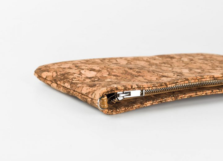 Zoom in on a cork pouch in a dark natural patched pattern, lying down, with a silver zip opening